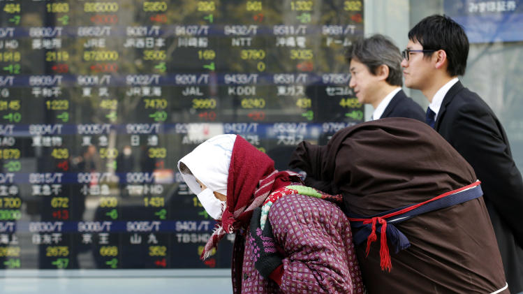 People walk by an electronic stock board of a securities firm in Tokyo, Monday, Jan. 21, 2013. Asian stock markets were mixed Monday amid uncertainty about the outcome of a central bank meeting in Japan and nervousness over whether U.S. political leaders will be able to reach a deal on the government's debt limit. (AP Photo/Koji Sasahara)