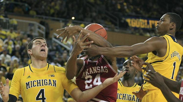 Michigan forward Mitch McGary (4) and teammate forward Glenn Robinson III (1) reach in on Arkansas guard Michael Qualls (24) during the first half of an NCAA college basketball game in Ann Arbor, Mich., Saturday, Dec. 8, 2012. (AP Photo/Carlos Osorio)