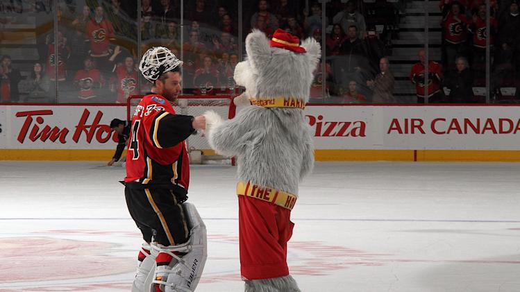 APRIL 17: Miikka Kiprusoff #34 of the Calgary Flames is congratulated by mascot Harvey the Hound after being named first star of the game against the Detroit Red Wings on April 17, 2013 at the Scotiabank Saddledome in Calgary, Alberta, Canada. (Photo by Brad Watson/NHLI via Getty Images)