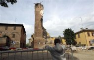 A boy looks at the damaged old tower of Delle Rocche castle after an earthquake in Finale Emilia