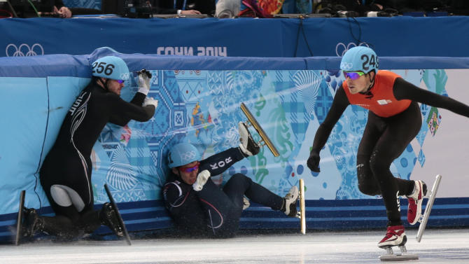 Lee Ho-suk of South Korea, left, and Eduardo Alvarez of the United States, centre, crash out alongside Freek Van Der Wart of the Netherlands as they compete in a men's 5000m short track speedskating relay semifinal at the Iceberg Skating Palace during the 2014 Winter Olympics, Thursday, Feb. 13, 2014, in Sochi, Russia