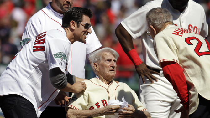 FILE - In this April 20, 2012, file photo, Boston Red Sox great Johnny Pesky, center, is greeted by former player Nomar Garciaparra, left, and others during a celebration of the 100th anniversary of the first regular-season baseball game at Fenway Park prior to the Red Sox taking on the New York Yankees in Boston. Pesky, who spent most of his 60-plus years in pro baseball with the Red Sox and was beloved by the team's fans, has died on Monday, Aug. 13, in Danvers, Mass. He was 92. (AP Photo/Elise Amendola, File)