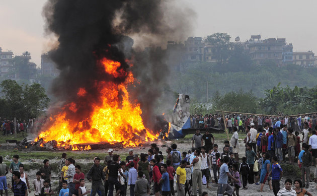 Nepalese gather around the burning wreckage at the crash site of a Sita Air airplane near Katmandu, Nepal, early Friday, Sept. 28, 2012. The plane carrying trekkers to the Everest region crashed and b