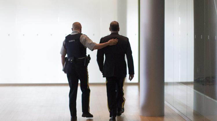 A Royal Canadian Mounted Police officer pats a colleague on the back before a press conference in Toronto as the RCMP announce the arrest of two men accused of plotting a terror attack on rail target on Monday April 22, 2013. (AP Photo/The Canadian Press, Chris Young)