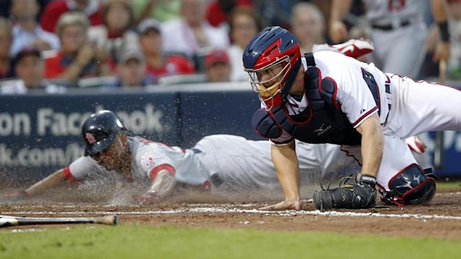 St. Louis Cardinals' Adron Chambers, left, crosses home plate after a bad throw from Atlanta Braves shortstop Andrelton Simmons (not shown) as Braves catcher David Ross, right, tries to make the catch during the seventh inning of the National League wild card playoff baseball game on Friday, Oct. 5, 2012, in Atlanta. (AP Photo/John Bazemore)