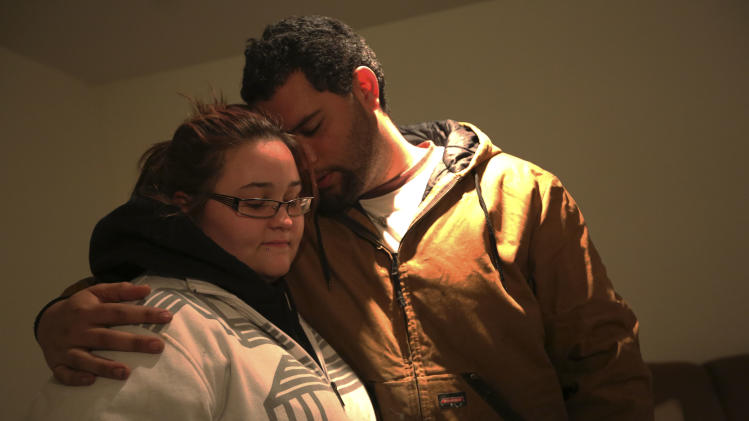 A couple embraces as they participate in a prayer meeting at the Heaven Ice Cream shop, Friday, Dec. 14, 2012 in Newtown, Conn. A gunman walked into the school Friday and opened fire, killing 26 people, including 20 children.  (AP Photo/Mary Altaffer)