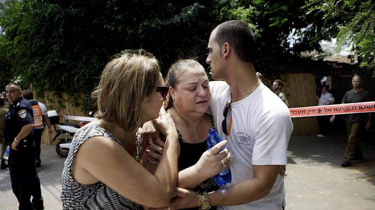 Israelis try to comfort a woman overcome by emotion after a rocket was fired by Palestinians militants from Gaza, in Yahud, central Israel, Tuesday, July 22, 2014. Israel has said its campaign, launched July 8, is aimed at stopping Hamas rocket fire into Israel — some 2,000 rockets have been launched over the past two weeks, the military says — and destroying tunnels the military says Hamas has constructed from Gaza into Israel for attacks against Israelis. (AP Photo/Dan Balilty)