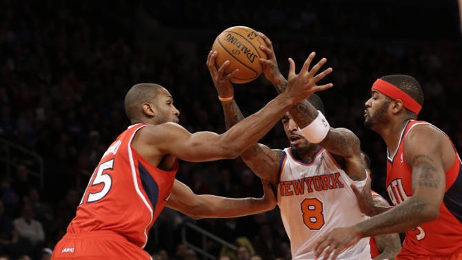 New York Knicks guard J.R. Smith (8) drives through Atlanta Hawks center Al Horford (15) and  forward Josh Smith (5) in the first half of  an NBA basketball game at Madison Square Garden in New York, Sunday, Jan. 27, 2013.  (AP Photo/Kathy Willens)