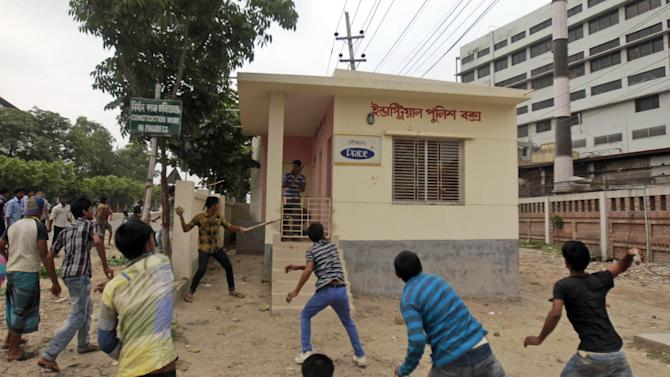 Bangladeshi garment workers throw stones and vandalize an industrial police control room during a protest against the collapse of an eight-story building that housed several garment factories and poor working conditions of the employees, in Dhaka, Bangladesh, Saturday, April 27, 2013. Police in Bangladesh took into custody five people in connection with the collapse of a shoddily-constructed building that collapsed this week, as rescue workers pulled out 19 survivors out of the rubble on Saturday and vowed to continue as long as necessary to find others despite fading hopes. (AP Photo/A.M. Ahad)