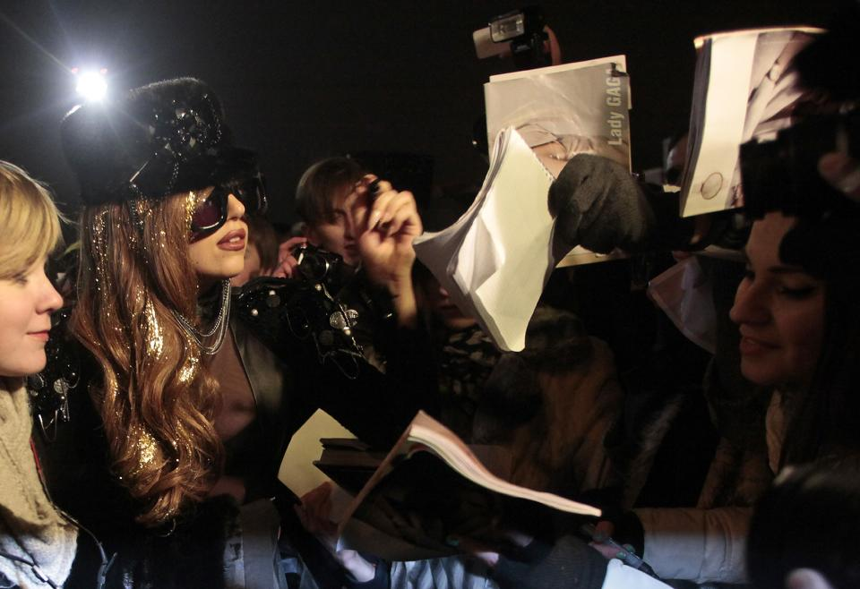 Lady Gaga, second left, signs autographs as she arrives at Vnukovo airport outside Moscow late Monday, Dec. 10, 2012. Lady Gaga, set to perform at Moscow's Olimpiisky stadium on Wednesday. (AP Photo/Pavel Golovkin)