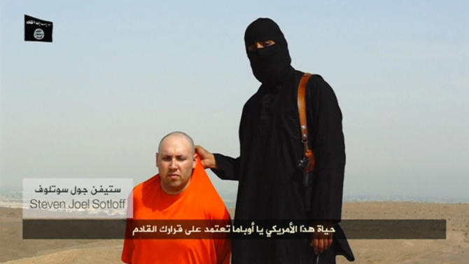 Still image from undated video of a masked Islamic State militant speaking next to man purported to be U.S. journalist Steven Sotloff at an unknown location