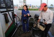 A motorcyclist fills up at a petrol station in Hefei, east China&#39;s Anhui province in May 2012. China said that it would slash fuel prices for the third time since May, after growth in the world&#39;s second largest economy slowed and softened demand