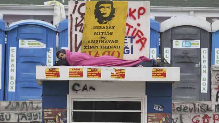 A protester sleeps atop of a bus operation booth as a woman passes by the Taksim Square in Istanbul, early Friday, June 14, 2013. A meeting between Turkey's Prime Minister Recep Tayyip Erogan and representatives of anti-government protesters ended early Friday without a clear resolution on how to end the occupation of a central Istanbul park that has become a flashpoint for the largest political crisis of his 10-year rule. (AP Photo/Thanassis Stavrakis)