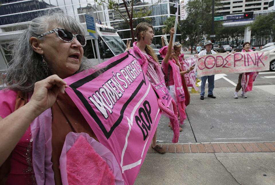 Karen Boyer, of Portland, Ore., displays her sign during a Code Pink protest before the Republican National Convention, Sunday, Aug. 26, 2012, in Tampa, Fla. (AP Photo/Dave Martin)