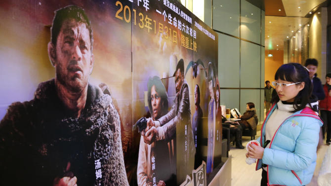"In this photo taken Wednesday, Feb. 13, 2013, a woman looks at an advertisement for the U.S. film ""Cloud Atlas"" at a movie theater, in Shanghai, China. Tens of millions of film fanatics are entering theaters around Asia during the long Lunar New Year holiday, but Hollywood can't count on them to boost the box office for its mostly serious Oscar nominees. Even with the Academy Awards buzz at a peak barely two weeks before the ceremony, patrons are opting for lighter fare. (AP Photo)"