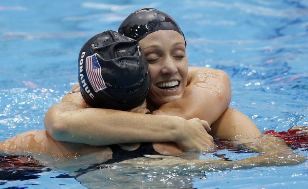 United States' Dana Vollmer embraces United States' Claire Donahue after Vollmer's gold medal win in the he women's 100-meter butterfly swimming final at the Aquatics Centre in the Olympic Park during the 2012 Summer Olympics in London, Sunday, July 29, 2012. (AP Photo/Daniel Ochoa De Olza)