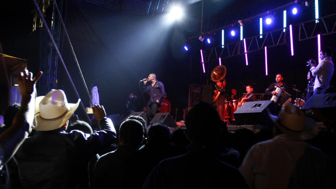 """FILE - In this Oct. 22, 2011 file photo, singer Alfredo Rios better known as """"El Komander"""" performs in concert at a rodeo in Naucalpan, Mexico. Rios is one of the best-known singers of the """"Altered Movement"""" genre whose lyrics frequently focus on shootouts, killings and guns. Mexican authorities seeking to ban drug ballads have levied one of their stiffest punishments yet against the music, fining concert promoters 100,000 pesos (almost $8,000) for a weekend performance by Rios in the northern city of Chihuahua. (AP Photo/Marco Ugarte, File)"""