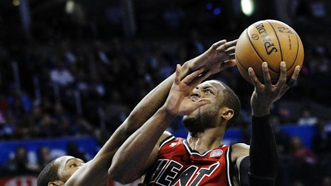 Miami Heat guard Dwayne Wade (3) is fouled by Oklahoma City Thunder forward Kevin Durant (35) as he shoots in the second quarter of an NBA basketball game in Oklahoma City, Thursday, Feb. 14, 2013. (AP Photo/Sue Ogrocki)