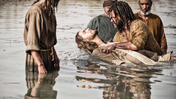 """This publicity image released by History shows Diogo Morcaldo as Jesus, center, being baptized by Daniel Percival, as John, in a scene from """"The Bible."""" The History network's first installment of the miniseries """"The Bible"""" was seen by 13.1 million people Sunday, March 3. The series, produced by the husband-and-wife team of Mark Burnett and Roma Downey, will air in four more installments concluding March 31, Easter Sunday. (AP Photo/History, Joe Alblas)"""