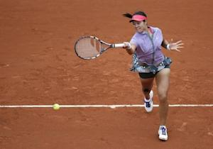 Li Na of China returns a forehand to Kristina Mladenovic of France during their women's singles match at the French Open tennis tournament at the Roland Garros stadium in Paris