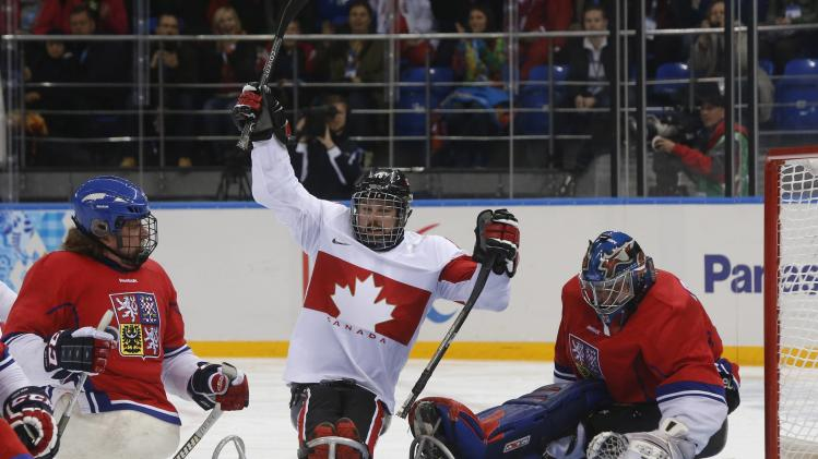 Canada's Bridges celebrates a goal against the Czech Republic's Michal Vapenka and Kvoch fights during their ice sledge hockey game at the 2014 Sochi Paralympic Winter Games