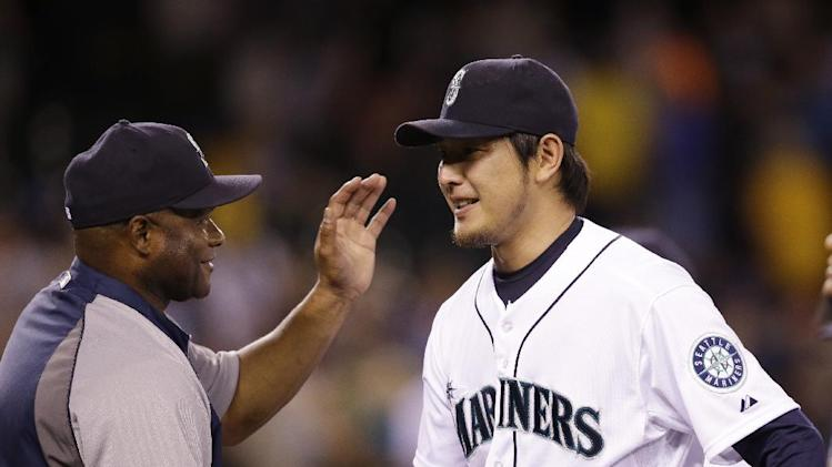 Seattle Mariners starting pitcher Hisashi Iwakuma, right, gets a pat from manager Lloyd McClendon after the team beat the Oakland Athletics in a baseball game Saturday, July 12, 2014, in Seattle. The Mariners won 6-2. (AP Photo/Elaine Thompson)