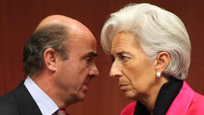 """International Monetary Fund managing director Christine Lagarde, right, talks with Spanish Economy Minister Luis de Guindos Jurado, during the Eurogroup finance ministers meeting in Brussels, Monday, Nov, 12, 2012. Greece's international lenders have prepared a """"positive"""" report on the country's reform efforts, a crucial step in its efforts to secure the next installment of its bailout loan, the head the of group of finance ministers from the 17 euro countries said Monday. (AP Photo/Yves Logghe)"""