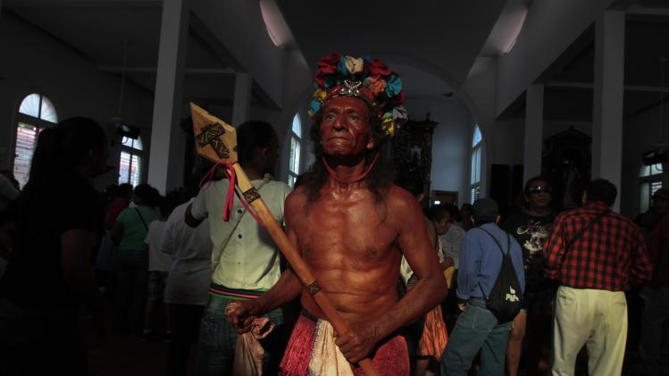 Man dressed as an indigenous person poses for pictures during celebrations honouring the patron saint of Managua