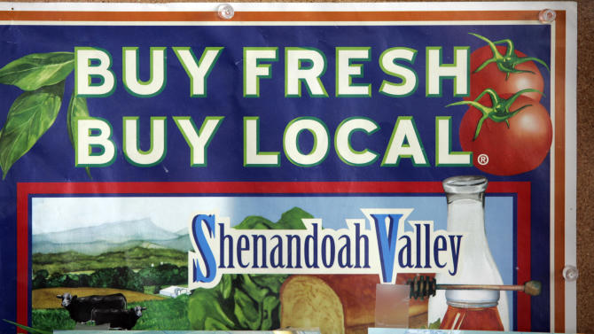 "FILE - In this July 15, 2008 file photo, a sign advocating buying fresh and local in the Shenandoah Valley is tacked on a bulletin board at the Shenandoah Valley Produce auction in Dayton, Va. A heightened consumer interest in produce grown nearby, which many assume to mean fresher food, fewer chemicals, and grown smaller farms, has led to popular use of the word on displays and menus. While good for many farmers, the trend can be misleading for consumers, as there is no one or regulated meaning for ""local"".  (AP Photo/Steve Helber, File)"