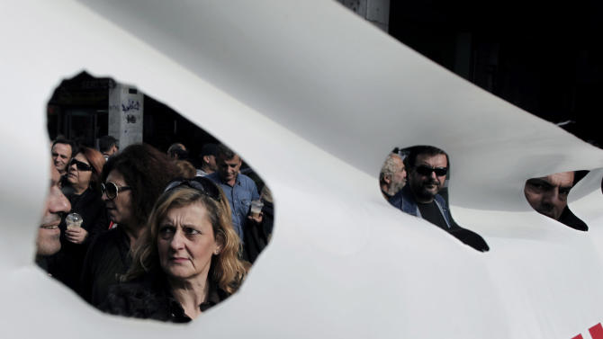 Municipal workers are seen through holes in a banner during a protest march to the ministry of Administrative Reform in central Athens, Tuesday, Nov. 27, 2012. Several hundred people took part in the peaceful demonstration. Greek municipal workers have occupied hundreds of town halls across the country to protest against government plans to suspend 2,000 civil servants for potential dismissal due to state budget cuts. (AP Photo/Petros Giannakouris)