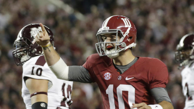 Alabama quarterback AJ McCarron (10) reacts after throwing a touchdown pass during the first half of an NCAA college football game at Bryant-Denny Stadium in Tuscaloosa, Ala., Saturday, Oct. 27, 2012. At left is Mississippi State linebacker Cameron Lawrence (10). (AP Photo/Dave Martin)