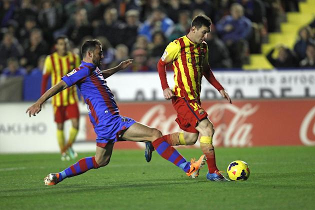 Barcelona's Lionel Messi from Argentina duels for the ball with Levante's Vyntra from the Czech Republic during their La Liga soccer match at the Ciutat de Valencia stadium in Valencia, Spain,