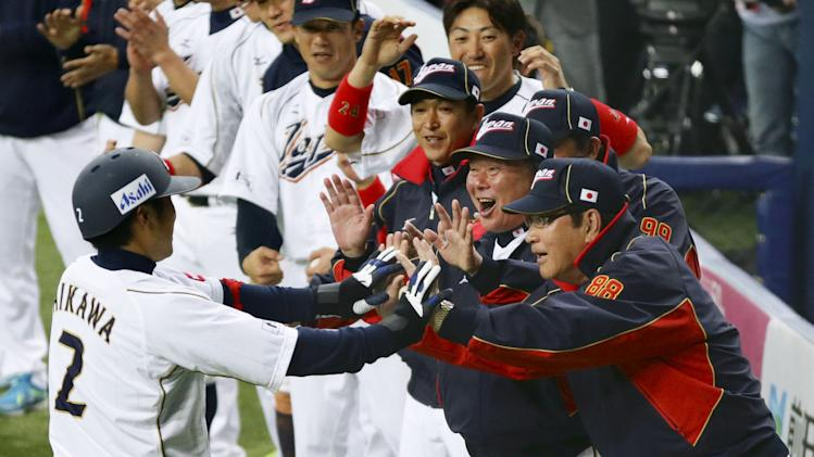FILE - In this Feb. 23, 2013 file photo, Japan's Ryoji Aikawa, left, is welcomed by manager Koji Yamamoto, right, and coach Osamu Higashio, second from right, after hitting a come-from-behind three-run homer against Australia in the eighth inning of their exhibition baseball game at Kyocera Dome in Osaka, western Japan. The team to beat in the third World Baseball Classic is two-time winner Japan. (AP Photo/Kyodo News) JAPAN OUT, MANDATORY CREDIT, NO LICENSING IN CHINA, HONG KONG, JAPAN, SOUTH KOREA AND FRANCE