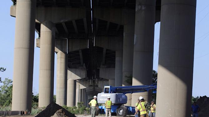 DelDot crew members surround a support column holding a span of the I-495 bridge over the Christina River Monday, June 2, 2014, after it shifted four degrees to the right prompting the closure of the span. The 4,800-foot bridge normally carries about 90,000 vehicles a day on I-495, which diverts traffic around the city of Wilmington and toward the Port of Wilmington. The route parallels Interstate 95, which runs through downtown Wilmington. (AP Photo/The Wilmington News-Journal, Kyle Grantham)