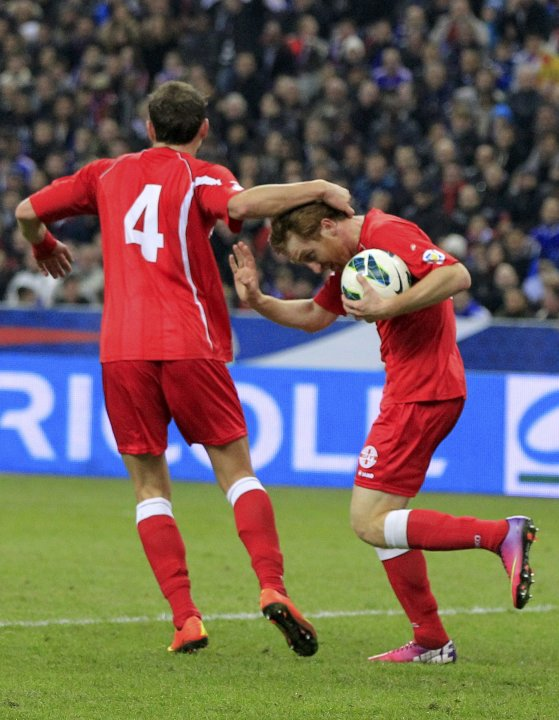 Georgia's Kobakhidze is congratulated by team mate Kashia after he scored against France during their 2014 World Cup qualifying match at the Stade de France stadium in Saint-Denis