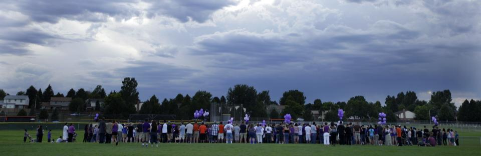 A crowd of people gather on an athletic field Saturday, July 21, 2012, at Gateway High School in Aurora, Colo., for AJ Boik, who was a student at the school and who was killed along with 11 others when a gunman opened fire in a movie theater. (AP Photo/Ted S. Warren)