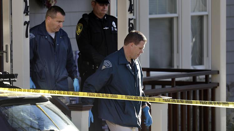 Law enforcement officials wearing gloves depart a home in Arlington, Mass., where four people were found dead on Monday, Nov. 18, 2013. Arlington Police Chief Frederick Ryan said the bodies of two adults and two infants were found at the residence Monday. (AP Photo/Steven Senne)