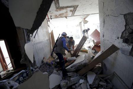 People salvage furniture from the rubble of a house destroyed by an air strike in Sanaa