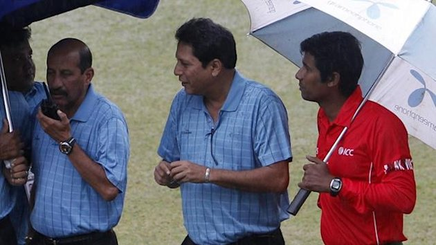 Umpires SK Tarapore (L), third umpire Nadir Shah (C) and their assistant Morshed Ali Khan (R) inspect the ground before rain postponed the second one-day international cricket match between New Zealand and Bangladesh in Dhaka October 8, 2010.