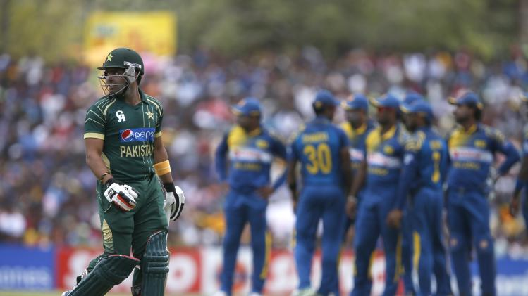 Pakistan's Akmal reacts as he walks off the field after his dismissal by Sri Lanka's Malinga during their final ODI cricket match in Dambulla