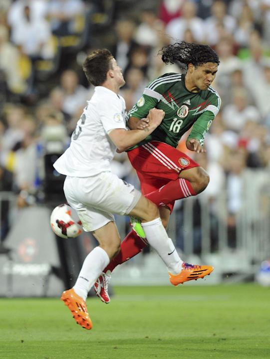 New Zealand's Michael McGlinchey, left, clashes with Mexico's Carlos Pena during their World Cup qualifying soccer match at Westpac Stadium, in Wellington, New Zealand, Wednesday, Nov. 20, 2013. Mexic