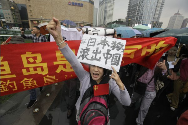 A demonstrator chants slogans while holding a sign during a protest against Japan's decision to purchase disputed islands, in Chengdu