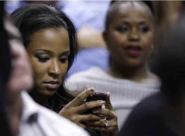 Savannah Brinson, the fiancee of Miami Heat's LeBron James, looks at her cell phone while watching an NBA basketball game between the Heat and the Atlanta Hawks, Monday, Jan. 2, 2012, in Miami. (AP Ph