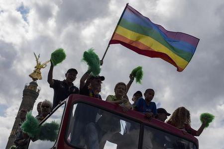 A reveller waves the gay pride flag as a float moves past the Siegessaeule victory column during Christopher Street Day parade in Berlin