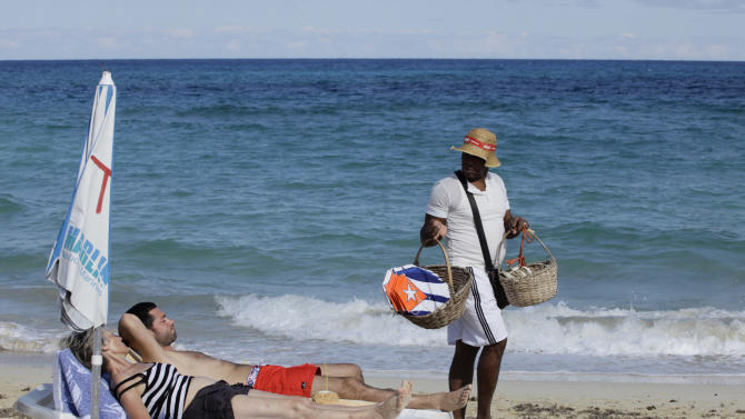"""In this Dec. 19, 2014 photo, tourists sunbathe as a vendor sells kites decorated with Cuba's flag on a beach near Havana, Cuba. The easing of tourism regulations is a gamble for both the U.S. and Cuba. Obama said Wednesday that people-to-people travel was a way to """"empower the Cuban people."""" At the same time, a U.S. tourism surge could funnel sorely needed cash to a tourism industry run mostly by what Obama described Friday as """"a regime that represses its people."""" (AP Photo/Desmond Boylan)"""