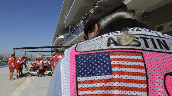 A photographer takes a picture as Ferrari driver Fernando Alonso of Spain gets a pit service during the first free practice session for the Formula One U.S. Grand Prix, at the Circuit of the Americas race track in Austin, Texas, Friday, Nov. 16, 2012.  (AP Photo/Luca Bruno)