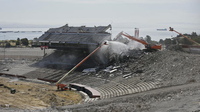 """Crews continue work on the demolition of Candlestick Park, Tuesday, June 30, 2015, in San Francisco. Very little remains of the park which was home to the San Francisco Giants baseball team and San Francisco 49ers NFL football team. Developers plan for houses, a hotel and a shopping center to be built on the site of the """"Stick,"""" which opened more than 50 years ago. (AP Photo/Eric Risberg)"""
