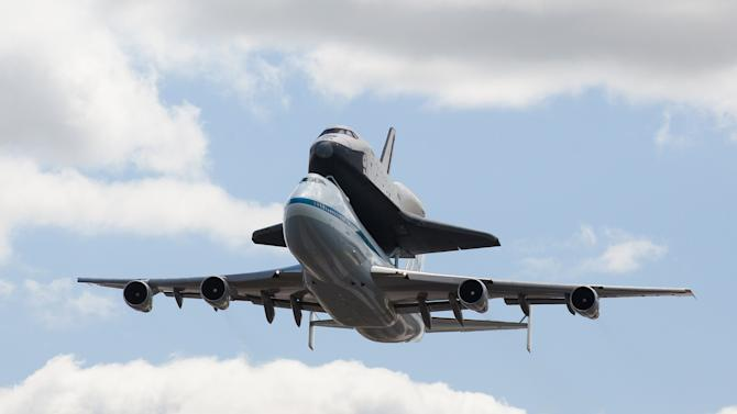FILE - In this April 27, 2012, file photo, space shuttle Enterprise, riding on the back of the NASA 747 Shuttle Carrier Aircraft performs a fly-by above JFK International Airport,  in New York.  Enterprise has been separated from the NASA 747 Shuttle Carrier at John F. Kennedy International Airport, just weeks after flying over New York City. Next month it will be taken by barge to the aircraft carrier USS Intrepid, the floating air-and-space museum that will be the shuttle's permanent home. The shuttle is scheduled to open to the public in mid-July. (AP Photo/John Minchillo, File)