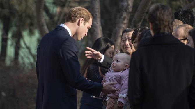 Britain's Prince William, Duke of Cambridge, looks at a child at the British Ambassador's official residence in Beijing