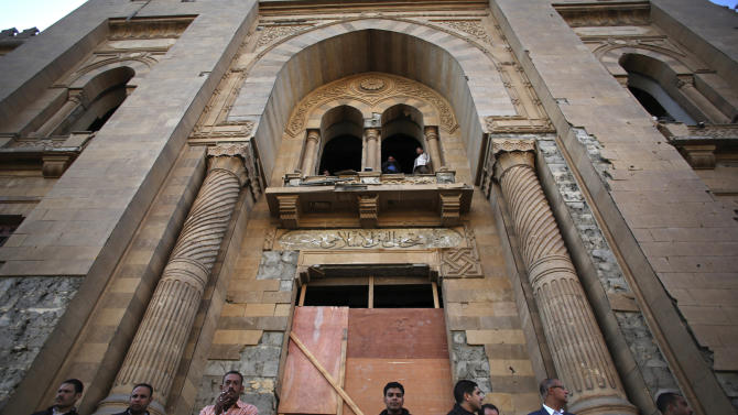 Egyptian security officers stand guard at the entrance of the Museum of Islamic Art after an explosion at the Egyptian police headquarters in downtown Cairo, Friday, Jan. 24, 2014. Egypt's antiquities minister says the car bombing that struck the main police headquarters in Cairo earlier in the day has caused major damage to the nearby Islamic art museum.(AP Photo/Khalil Hamra)